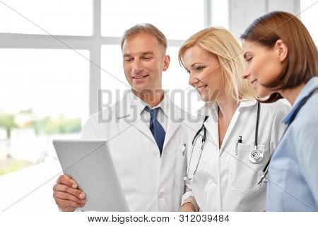 healthcare, medicine and technology concept - group of doctors with tablet computer at hospital