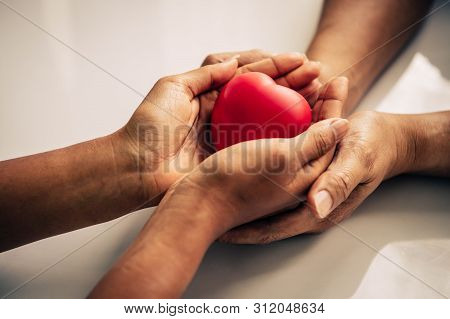 Helping Hand Of Heart Donor For Patient In Heart Disease. Man Give Red Heart To Woman As Couple. Peo
