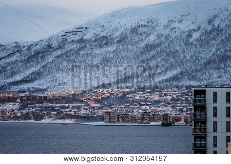 Residential Hillside Houses In Tromso Suburb Covered In A Deep Snow At Dusk, Norway