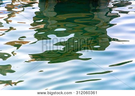Water Texture Background Close Up. Bright Colorful Water Reflection.