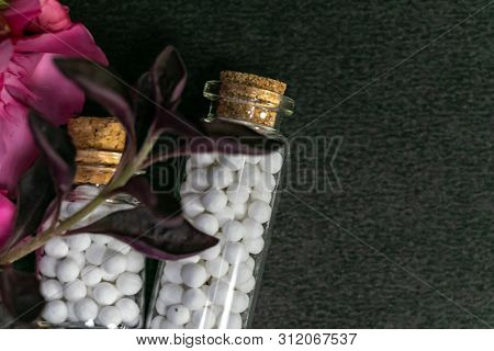 Close Up Image Of Two Homeopathic Medicine Bottles Consisting Of Pills With Pink Flowers On Dark Bac