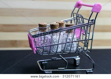 Shopping Cart Filled With Homeopathic Glass Bottles With Cork On Wood And Dark Background. Online Ho