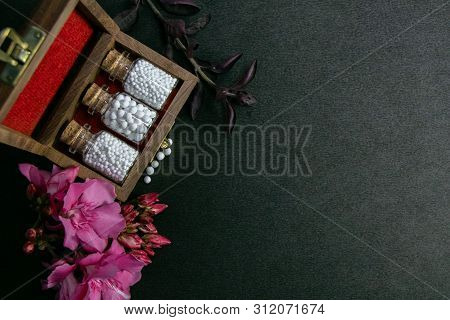 Top View Of Homeopathic Pills Bottles With Cork In Wooden Classic Box And Pink Flowers On Dark Backg