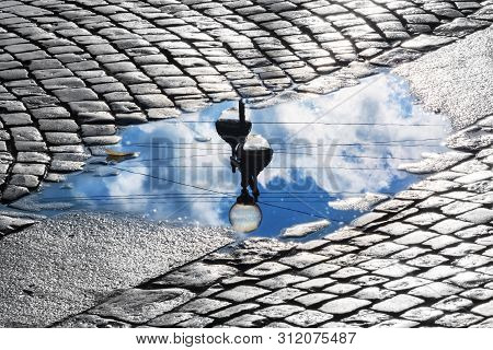 Lantern And Sky Reflection In The Puddle