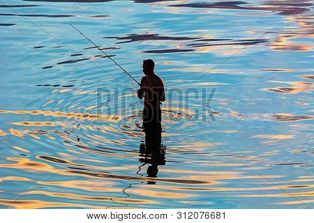 Silhouette Of A Fisherman In Reflection In Water Ripples