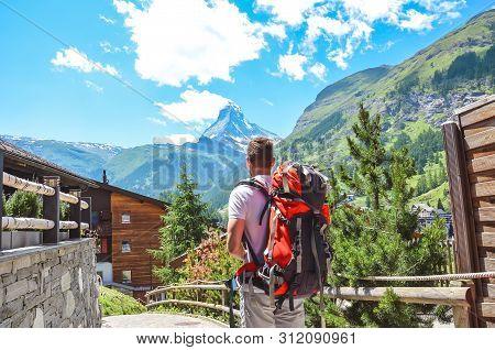 Caucasian Man Hiking In Beautiful Zermatt, Switzerland. Matterhorn In Background. Backpacking Lifest