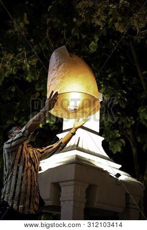 Man Releasing Paper Lantern During Loy Krathong And Yi Peng In Chiang Mai - Thailand