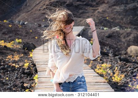 Girl Walking On Windy Wooden Path With Hair On Her Face