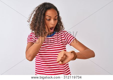 Young brazilian woman wearing red striped t-shirt standing over isolated white background Looking at the watch time worried, afraid of getting late