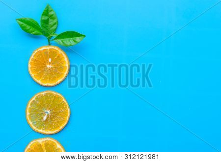 Summer Of Slice Orange Fruit With Green Leaves On Blue Background.