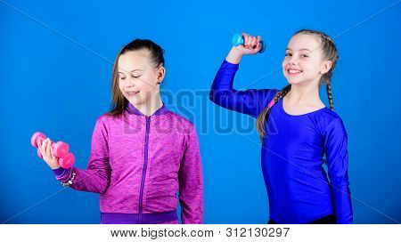Sporty upbringing. Easy exercises with dumbbell. On way to stronger body. Girls exercising with dumbbells. Beginner dumbbells exercises. Children hold dumbbells blue background. Sport for teens poster