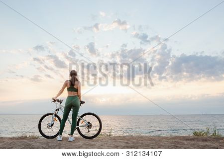 Portrait Of A Beautiful Young Brunette Woman Resting After Bicycle Ride At Sunrise. Model Listening