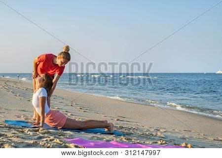 Yoga Trainer. Yoga Class Instructor Helps Beginner To Make Asana Exercises. Woman Doing Yoga With Tr