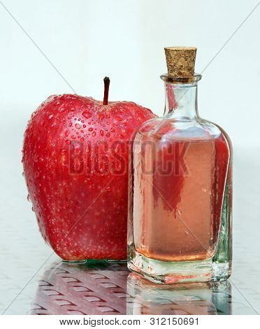 Still Life With Fresh Compote In Vintage Glass Botlle And Red Ripe Apple Against A High Key Backgrou