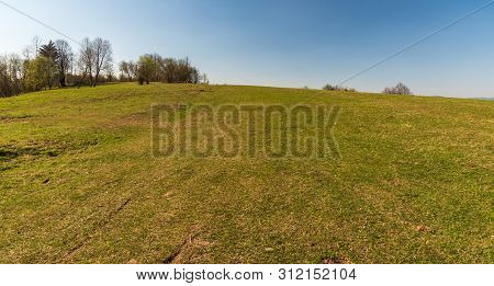 Springtime Meadow With Few Trees And Clear Sky In Javorniky Mountains Above Cadca City In Slovakia