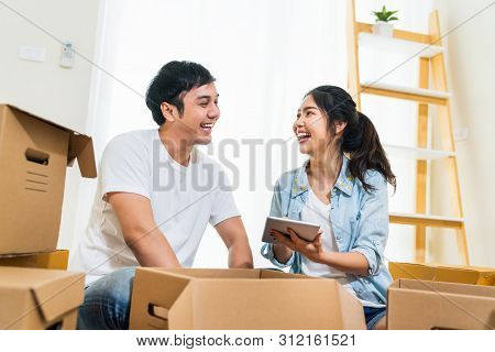 Happy Young Asian Couple Moving In To New House, Using Digital Tablet Organizing Things And Unpackin