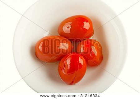 Four Marinated Tomatoes On A White Plate
