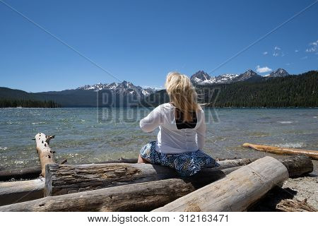 Blonde Woman With Back Facing Camera Looks Out To The Sawtooth Mountains While Sitting On Logs At Re