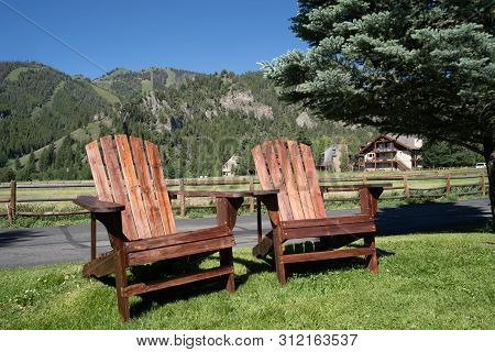 Two Empty Wood Adirondack Chairs Sit On Grass, Overlooking The Sawtooth Mountains Of Idaho. Taken In