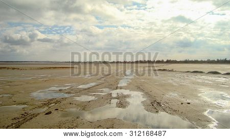 Desert Parched Estuary. In The Rare Puddles Reflected The Clouds. In The Sky Clouds.   A Flat Horizo