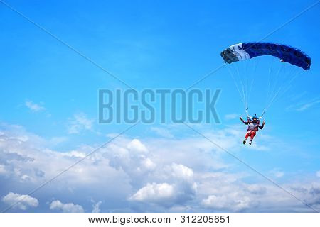 Skydiver With A Blue Canopy Of A Parachute On The Background A Blue Sky And Clouds, Close-up. Skydiv