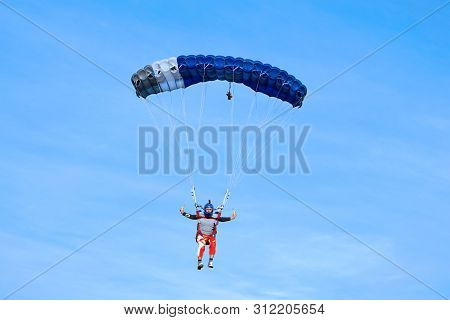 Skydiver With A Blue Canopy Of A Parachute On The Background A Blue Sky, Close-up. Skydiver Under Pa