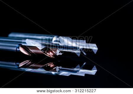 Special Tools Isolated On Black Background. Made To Order Special Tools. Coated Step Drill And Reame