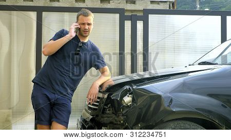 Car Accident Concept. Man In A State Of Shock Talking On The Phone After A Car Accident, Standing By