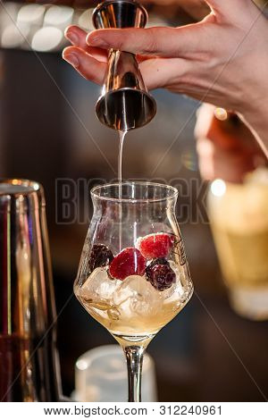 Barman Makes A Beautiful Cocktail At The Bar. The Barman Whipped The Cocktail. Blurred Bar. Space.