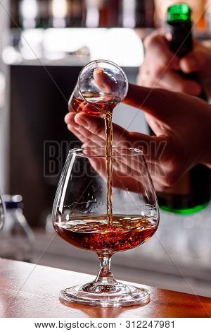 Bartender Pours Cognac Into A Glass Snifter Behind A Wooden Bar Counter Against A Blurred Bar. Close