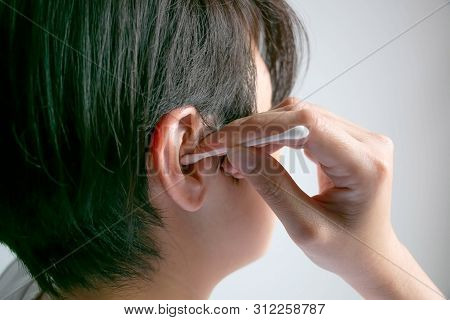 Close-up image  in right side of woman is cleaning her ear with cotton bud; concept of health care and body hygiene. poster