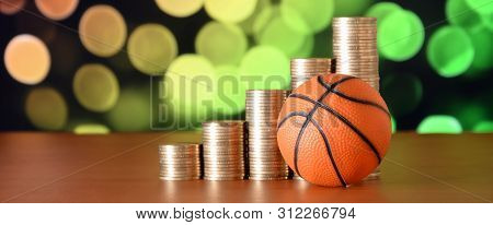 Basketball And Stacks Of Golden Coins In Growth Graph On The Blurred Bokeh Background