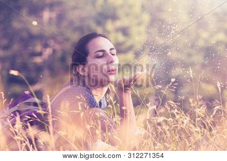 Woman Blow Dust From Hand In Sunset. Healthy People Lifestyle. Woman Blow Dust From Hand. Nature Lif
