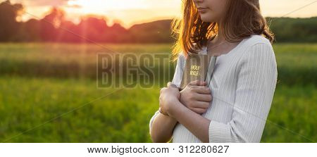 Christian Teenage Girl Holds Bible In Her Hands. Reading The Holy Bible In A Field During Beautiful