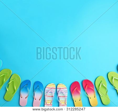 Different Flip Flops And Space For Text On Blue Background, Flat Lay. Summer Beach Accessories