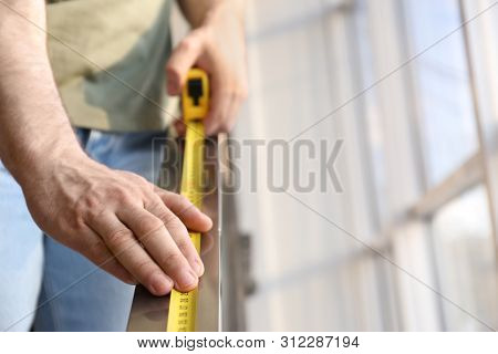 Man Measuring Metal Railing, Closeup View With Space For Text. Construction Tool