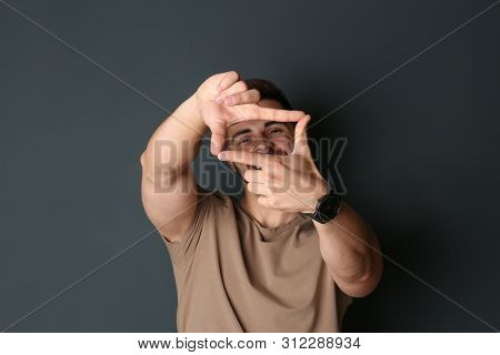 Portrait Of Happy Man Making Frame With Hands On Dark Background