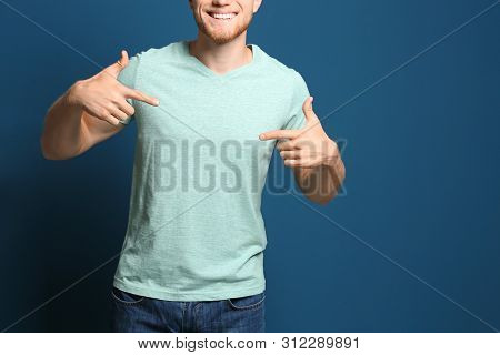 Young Man Wearing Blank T-shirt On Blue Background, Closeup. Mockup For Design