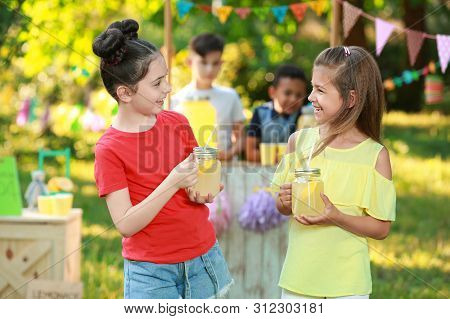 Cute Little Girls With Natural Lemonade In Park. Summer Refreshing Drink