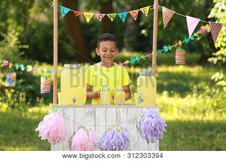 Cute Little African-american Boy At Lemonade Stand In Park. Summer Refreshing Natural Drink