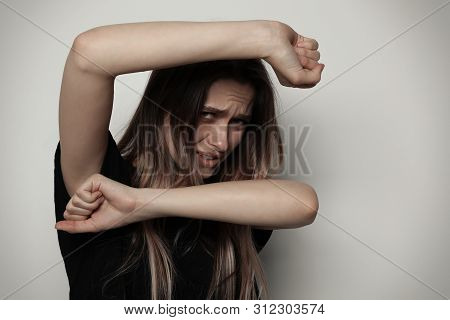Portrait Of Woman Protecting Herself On Light Background. Stop Violence