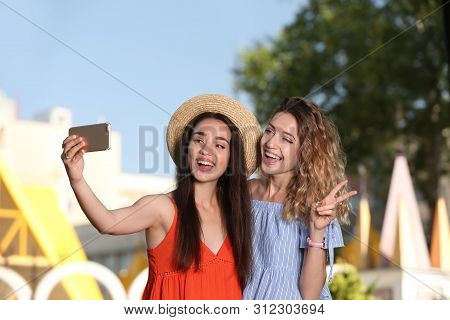 Happy Young Women Taking Selfie Outdoors On Sunny Day