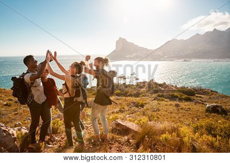 Young adult friends on a hike celebrate reaching a summit near the coast, full length, side view poster
