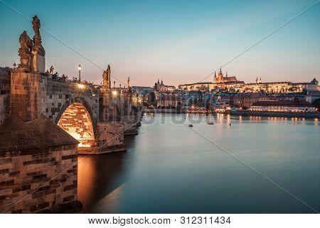 Prague Castle And Charles Bridge In The Evening, Prague, Czech Republic, Vltava River In Foreground.