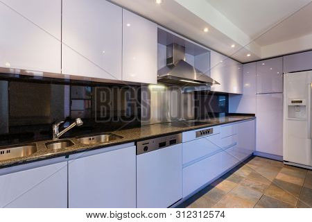 Modern lilac kitchen in luxury loft with modern appliances. No one inside