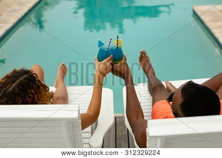 High angle view of diverse couple toasting glasses of cocktail while relaxing on a sun lounger near swimming pool at the backyard of home. Summer fun at home by the swimming pool