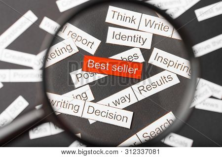 Magnifier Glass Over The Red Inscription Best Seller Cut Out Of Paper. Surrounded By Other Inscripti