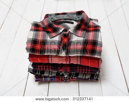 Stack Of Plaid Shirts On A White Wooden Background. Clothing Concept.