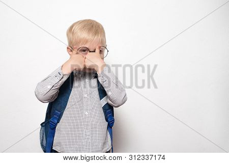 Portrait Of A Blond Boy In Glasses And With A School Backpack On A White Background Shows A Gesture