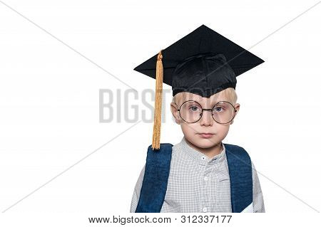 Portrait Of A Cute Blond Boy In Big Glasses, Academic Hat And A School Bag. White Background. Place